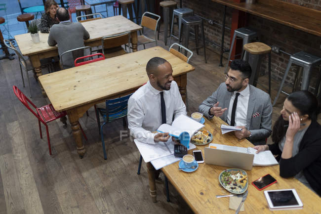 Business people talking and eating, working in cafe — Stock Photo