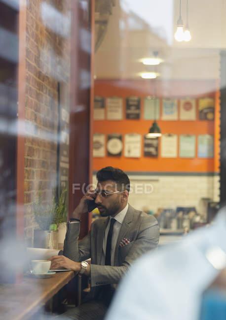 Uomo d'affari che parla con lo smart phone, lavora al bar — Foto stock
