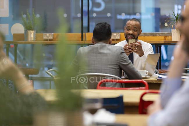 Uomini d'affari con smart phone che lavorano nel caffè — Foto stock