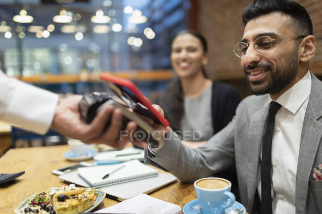 Businessman paying with smart phone contactless payment in cafe — Stock Photo