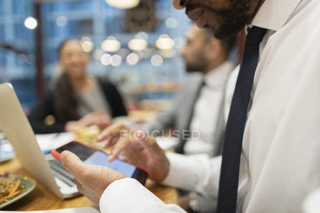 Close up businessman using smart phone in cafe — Stock Photo