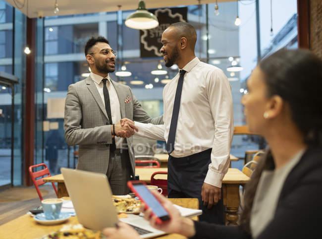 Бізнесмени рукостисканням, працюють в кафе — стокове фото