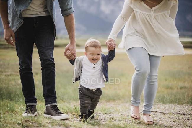 Pais caminhando com filho bebé no campo — Fotografia de Stock