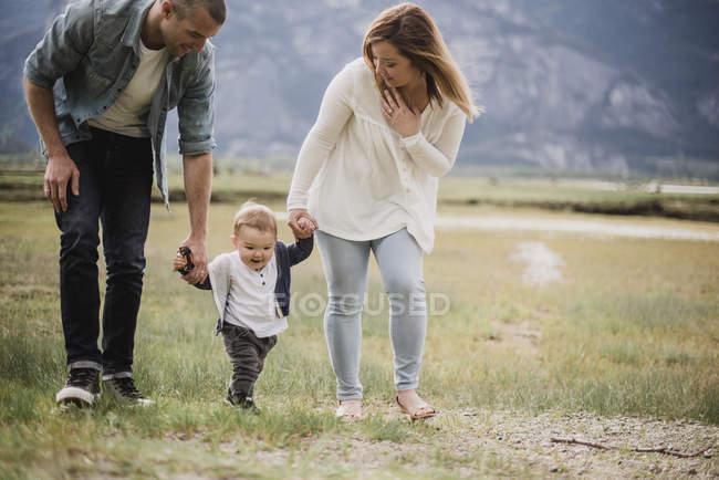 Pais caminhando com filho bebé no campo rural — Fotografia de Stock