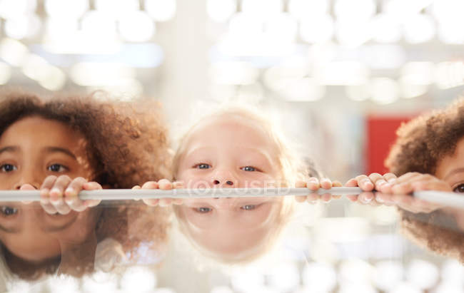Portrait cute kids peeking from behind counter — Stock Photo