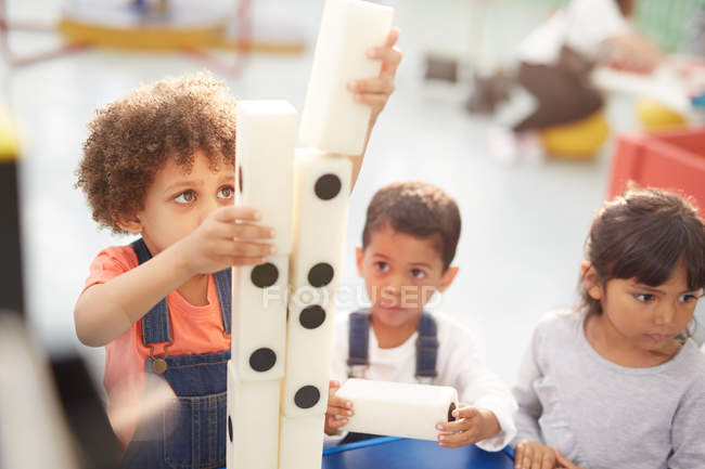 Curious kids stacking large dominos at interactive exhibit in science center — Stock Photo