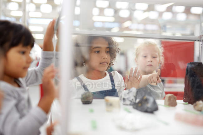 Curious kids looking at rocks in display case in science center — Stock Photo