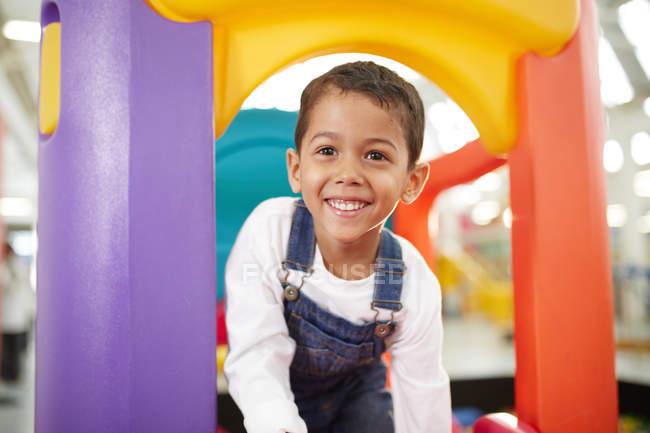 Portrait cute boy playing on slide — Stock Photo