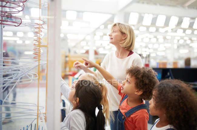 Вчитель і цікаво студенти дивляться виставлятися в науковому центрі — стокове фото