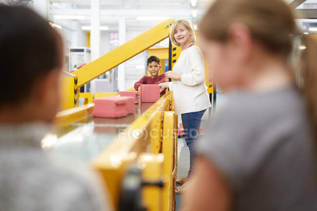 Teacher and students playing at interactive construction exhibit in science center — Stock Photo
