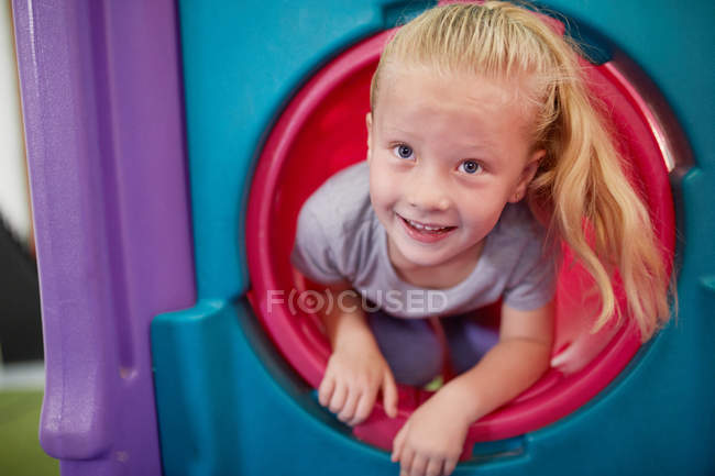 Portrait cute, happy girl playing in tube slide — Stock Photo
