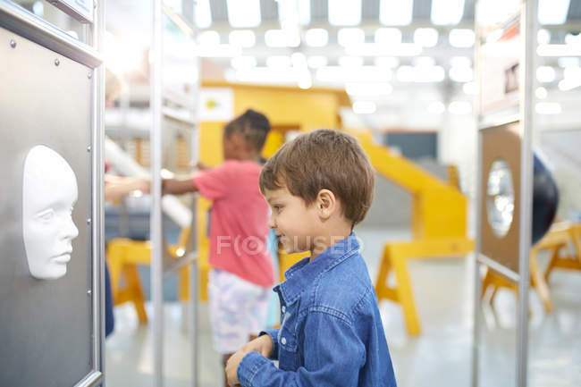 Curious boy looking at face in science center — Stock Photo