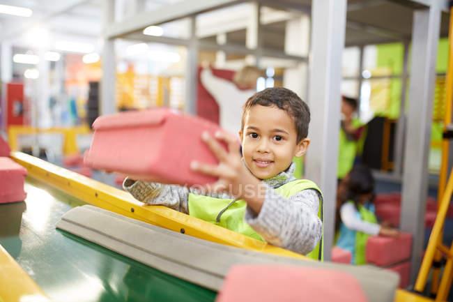 Ritratto sorridente ragazzo impilamento schiuma mattoni costruzione interattiva per mostre nel centro di scienza — Foto stock