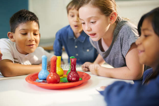 Curious kids watching multicolor foam in beakers — Stock Photo