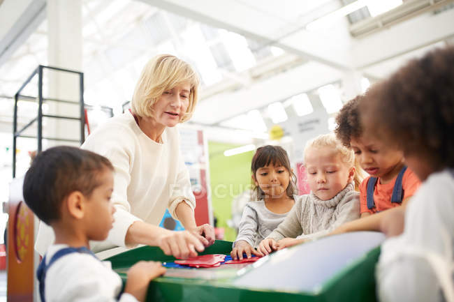 Teacher and students at interactive exhibit in science center — Stock Photo