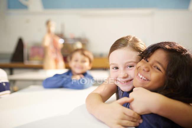 Portrait affectionate, cute schoolgirls hugging — Stock Photo