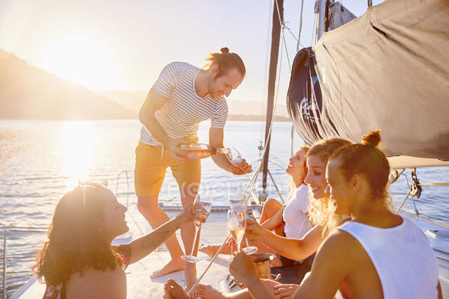 Friends drinking champagne on sunny catamaran — Stock Photo