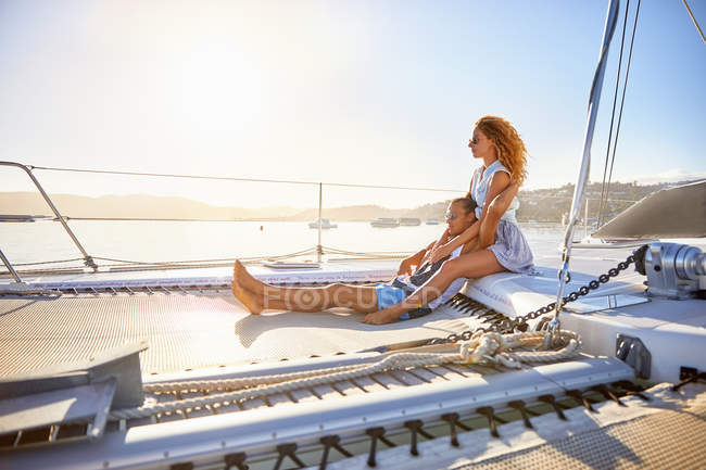 Serene, affectionate couple relaxing on sunny catamaran — Stock Photo