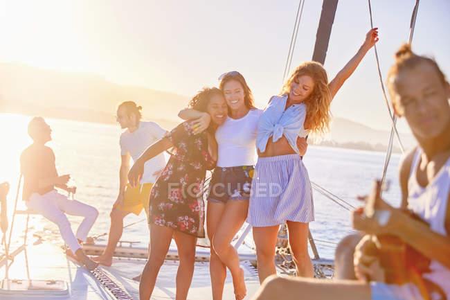 Playful women friends dancing on sunny catamaran — Stock Photo