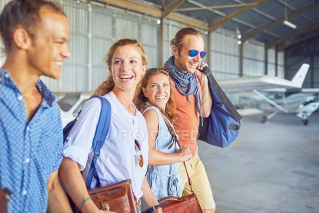 Amigos felices caminando en el hangar del avión - foto de stock