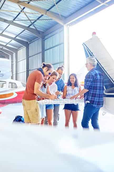 Друзья, планирование поездки на карте в самолет ангар — стоковое фото