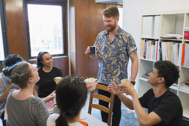 Creative business people enjoying coffee and tea in office — Stock Photo