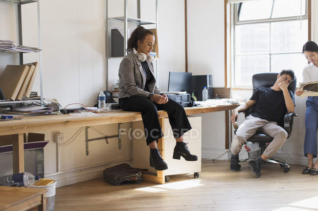Creative businesswoman with headphones sitting on desk in office — Stock Photo
