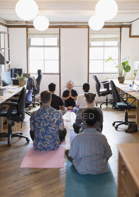 Creative business people meditating in office — Stock Photo