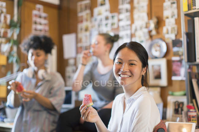 Portrait smiling creative businesswoman eating watermelon in office — Stock Photo