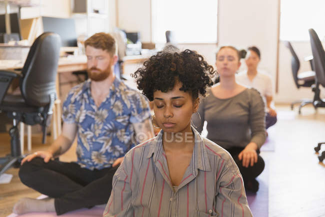 Serene creative business people meditating in office — Stock Photo
