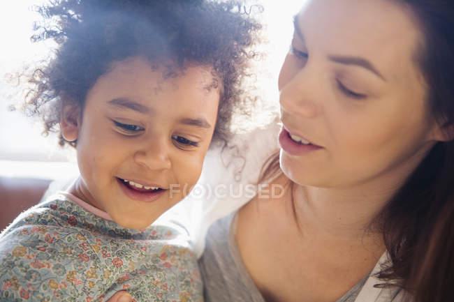 Закройте ласковые мать и дочь глядя вниз — стоковое фото