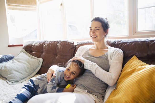 Mãe afetuosa e filho da criança abraçando no sofá da sala de estar — Fotografia de Stock