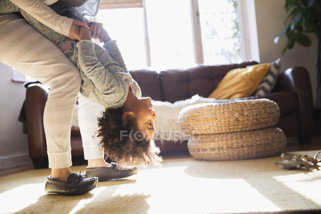 Mother holding daughter upside-down in living room — Stock Photo