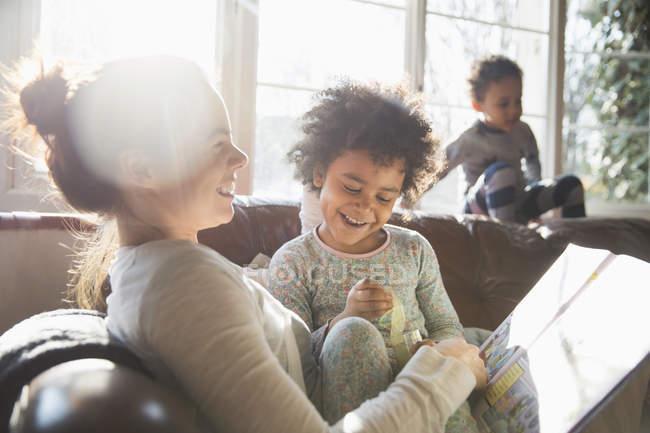 Счастливая мать и дочь обнимаются, читают книгу на диване в солнечной гостиной — стоковое фото