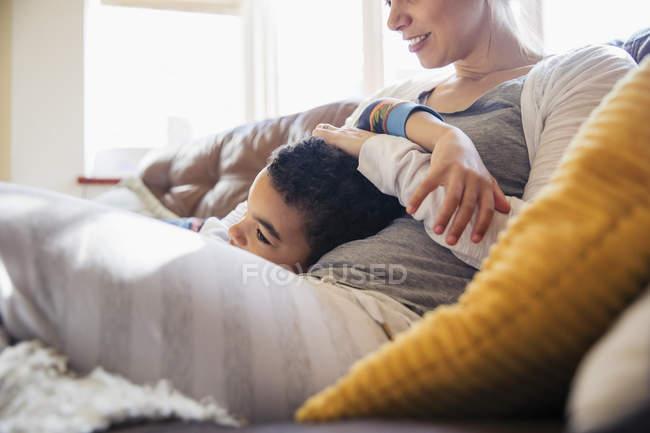 Carinhoso mãe e filho abraçando no sofá — Fotografia de Stock