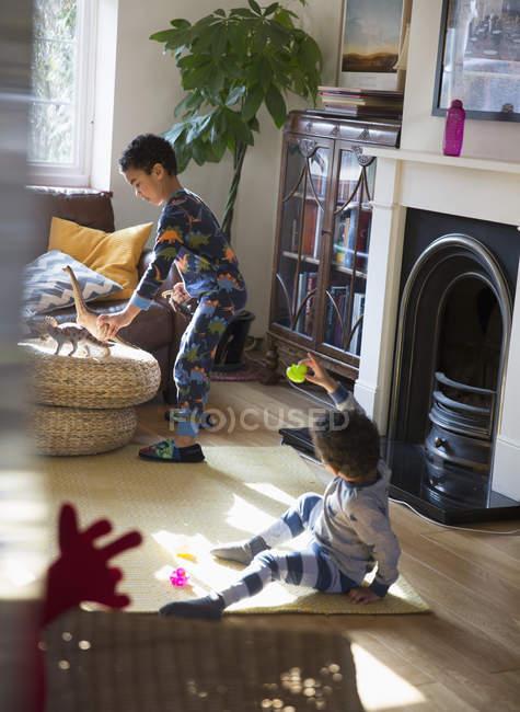 Irmãos em pijama brincando com brinquedos na sala de estar — Fotografia de Stock