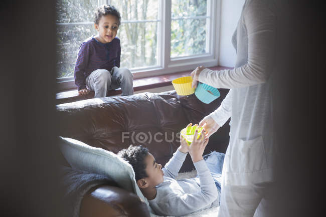 Mãe dando lanches para crianças na sala de estar — Fotografia de Stock