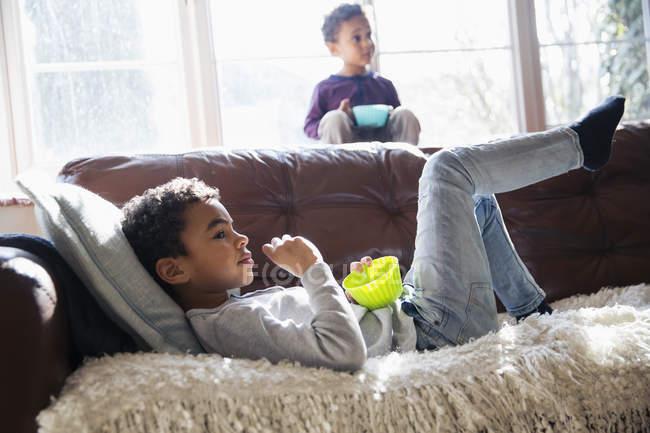 Irmãos relaxantes, assistindo TV e desfrutando de lanche no sofá da sala de estar — Fotografia de Stock