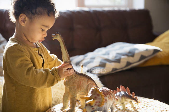 Innocent boy playing with dinosaur toys — Stock Photo