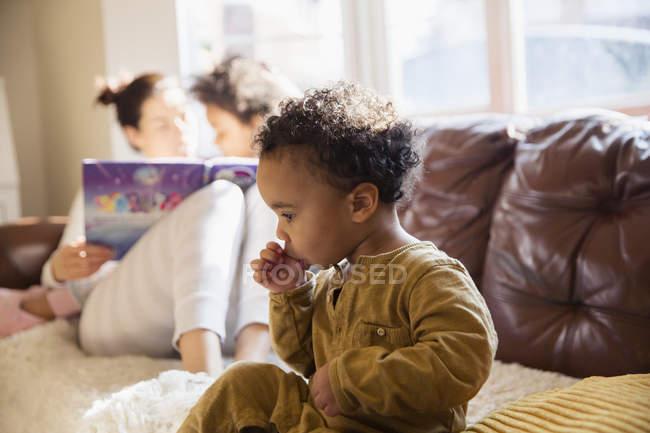 Unschuldiger kleiner Junge lutscht Daumen auf Sofa — Stockfoto