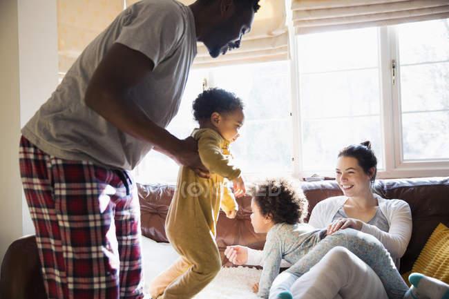 Família multi-étnica brincalhão em pijama na sala de estar — Fotografia de Stock