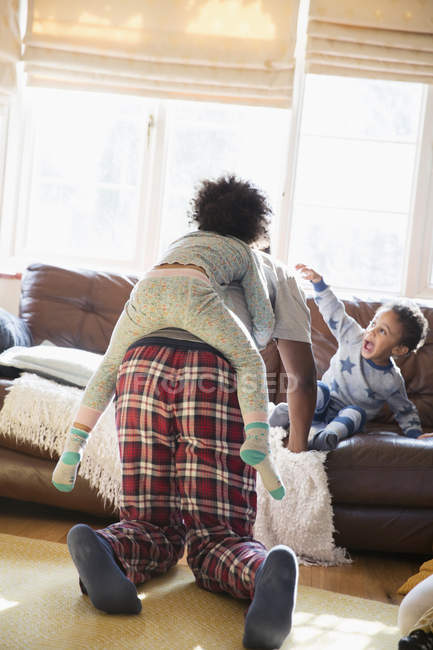 Father and kids in pajamas playing in living room — Stock Photo