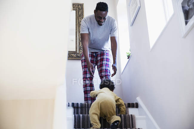 Father in pajamas watching baby son crawling up stairs — Stock Photo