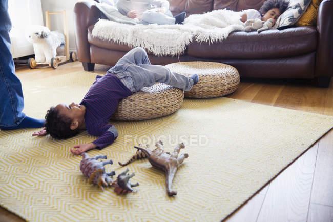 Verspielter Junge mit Dinosaurier-Spielzeug auf Wohnzimmerboden — Stockfoto