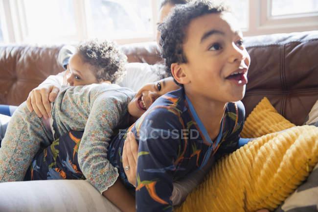 Jovem família brincalhona e afetuosa em pijama no sofá da sala de estar — Fotografia de Stock