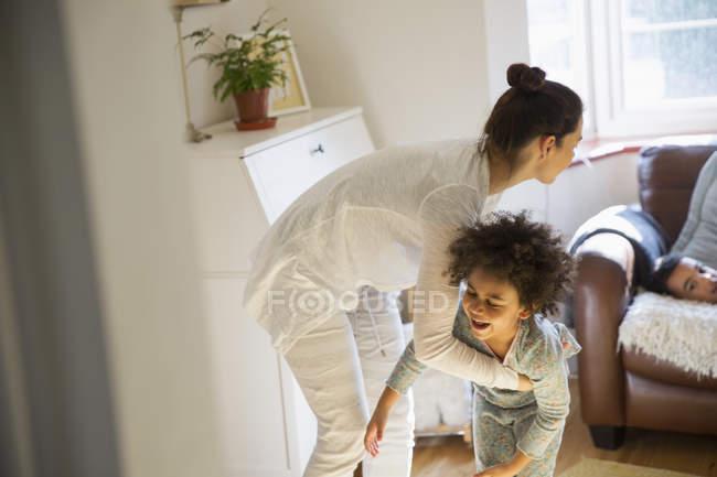 Mãe e filha brincalhão em pijama — Fotografia de Stock