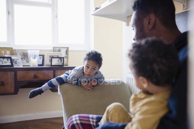 Brincalhão, menino inocente escalando em móveis — Fotografia de Stock