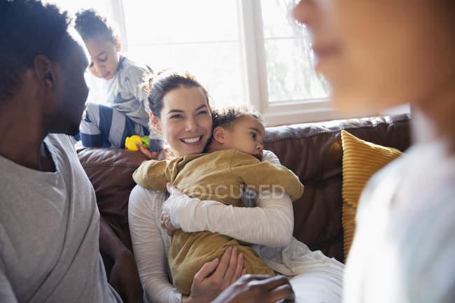 Mãe feliz abraçando o bebê filho, relaxando com a família no sofá da sala de estar — Fotografia de Stock