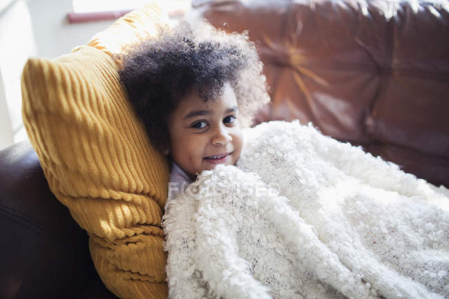 Portrait cute girl relaxing, cuddling on sofa with blanket and pillow — Stock Photo