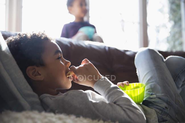 Menino comendo lanche e assistindo TV no sofá — Fotografia de Stock